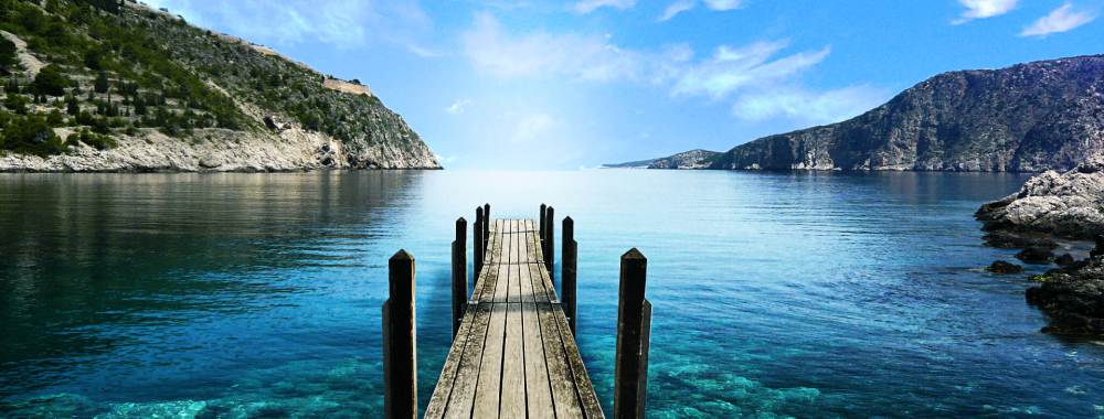 An old wooden dock extending out over the calm water of a bay on a sunny day.