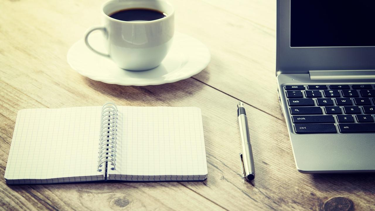A cup of coffee, an open notebook with a pen, and the side of a laptop are visible on a wooden table.