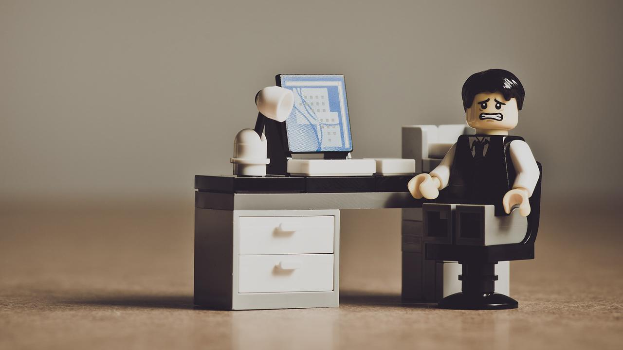 Lego figure sitting at a desk with a look of despair on his face.