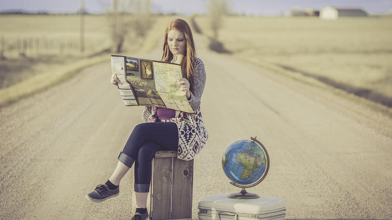 A white woman sits on a suitcase in the middle of the road contemplating a map while a world globe sits on top of a smaller suitcase next to her.