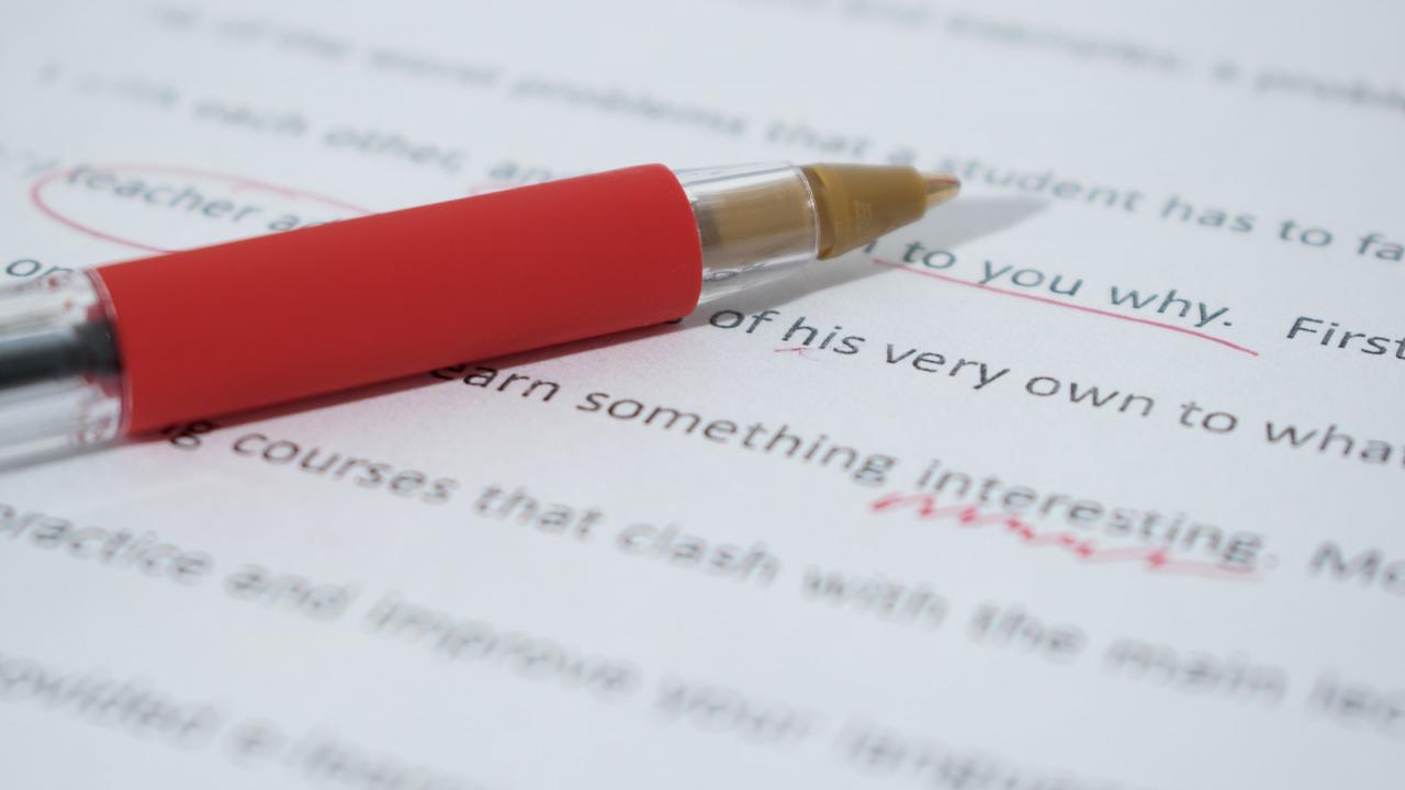 A red pen resting on a marked up page showing corrections to typed text.