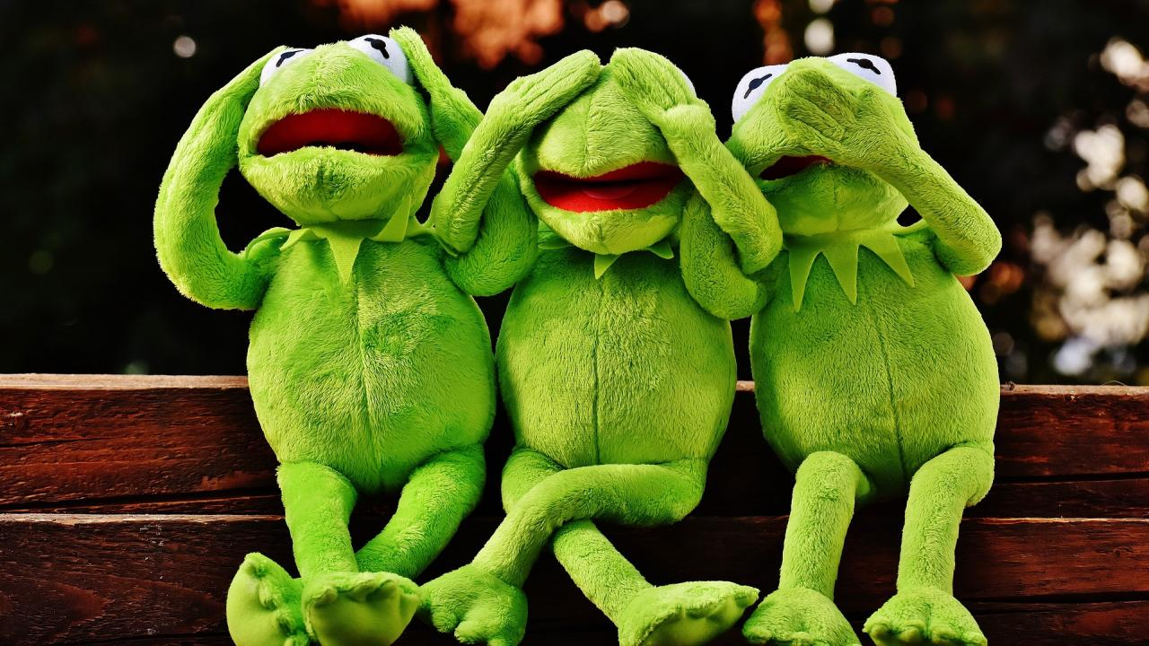 Three Kermit the Frog dolls sitting in the 'see no evil, hear no evil, speak no evil' pose.