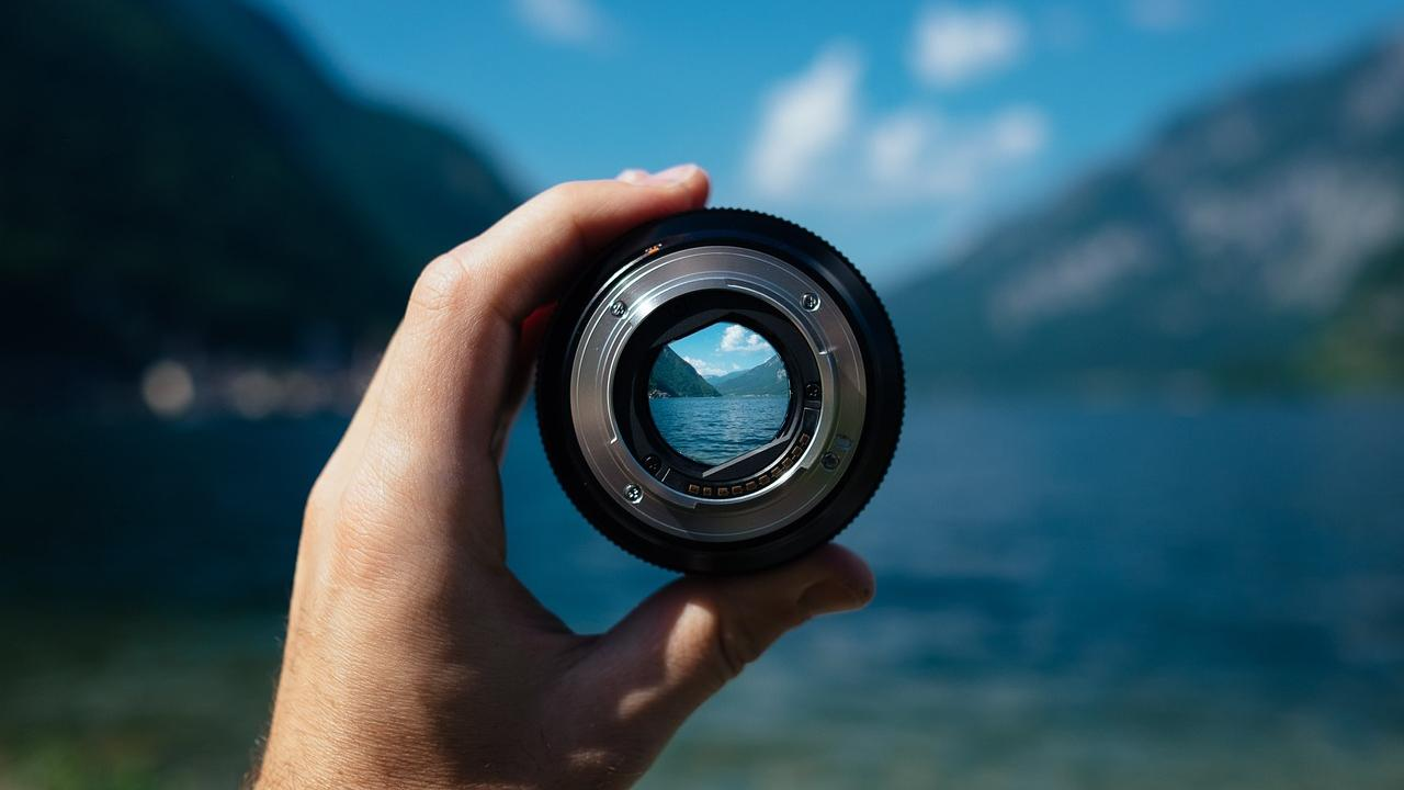 A person's hand hold up a camera lens through which you can see a crisp view of the ocean and steep hillsides while the area outside the lens is blurred.