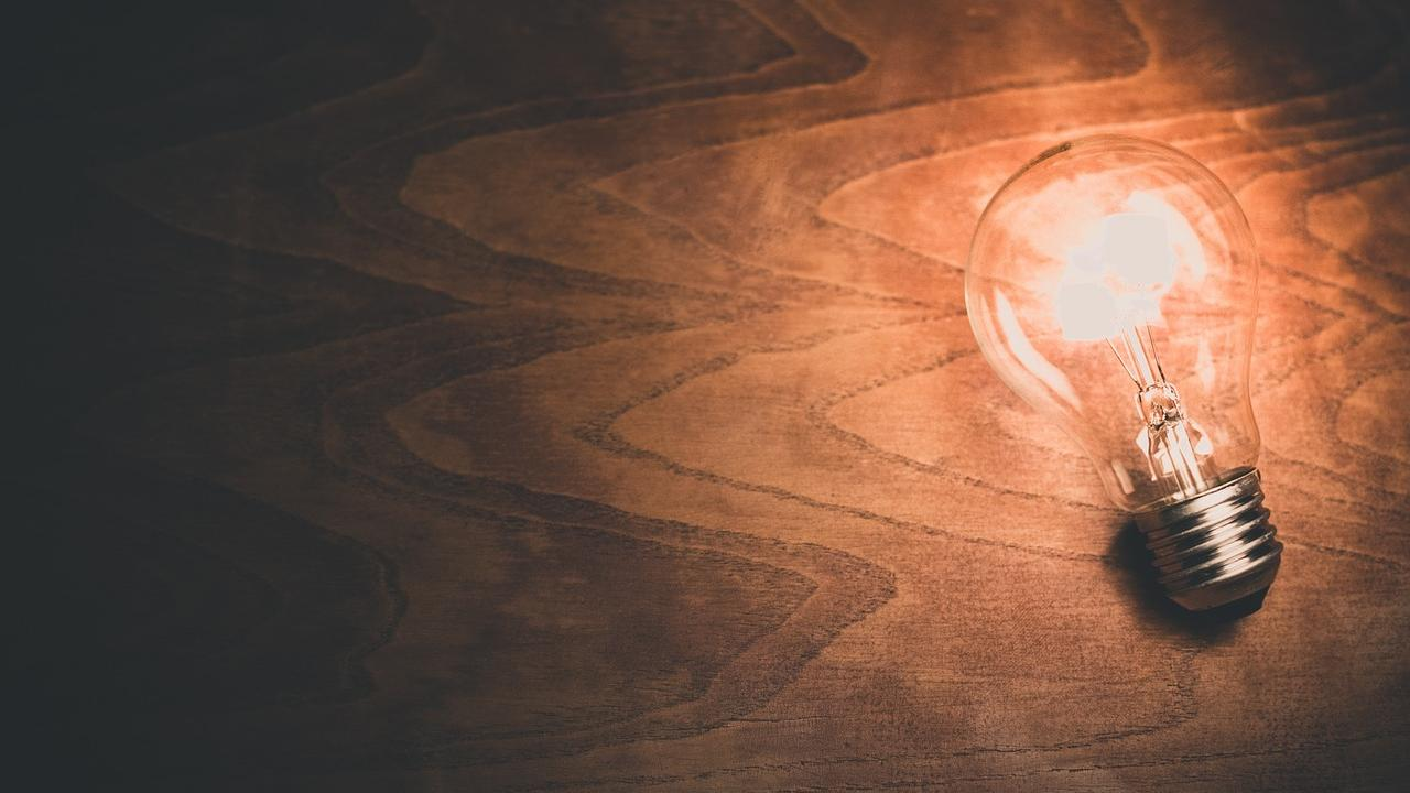 A bright light bulb on top of a wooden background
