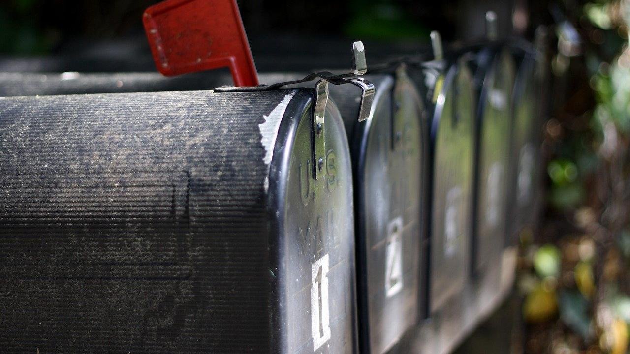 A series of mailboxes, the first one with its flag set in the up position.
