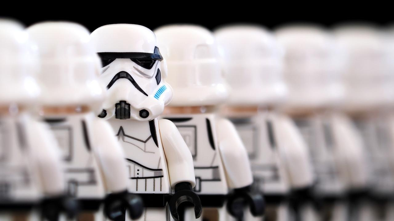 A row of Lego Stormtroopers, all of them facing away from the viewer except for a single one facing forward.""