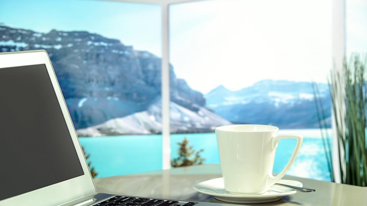 A laptop and coffee sit in the foreground. Beyond is a large window overlooking a lake with mountains in the background.