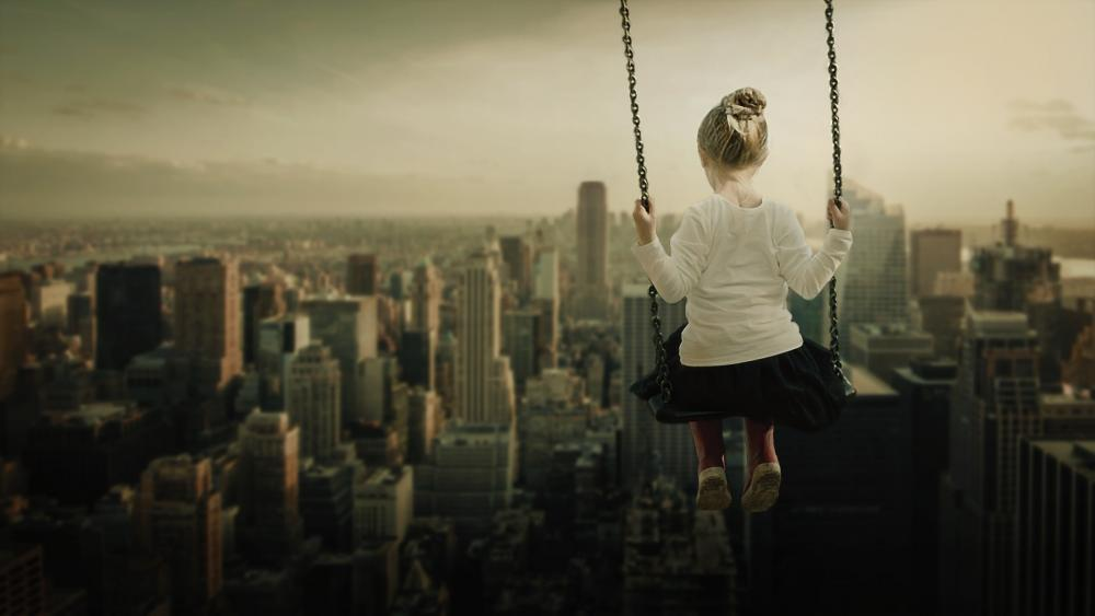 A sepia toned photo of a little girl on a swing with the unusual perspective of swinging over the New York skyline.