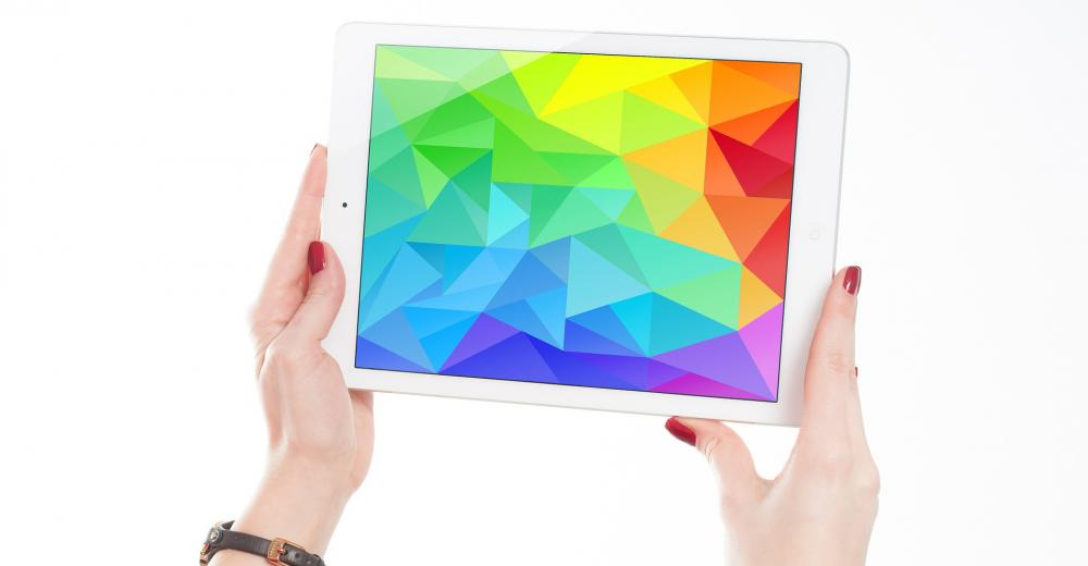 A woman's hands holding up an ipad with a screen displaying a full spectrum of color.