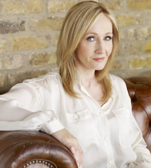 JK Rowling sitting on a red leather couch