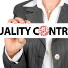 "A woman in a business suit holding a sign reading ""Quality Control"""
