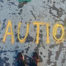 Photo by Goh Rhy Yan on Unsplash. The word 'Caution' is written on the ground.