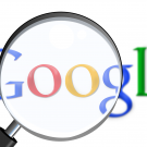 The Google logo with a magnifying glass in front of it.