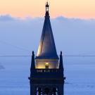 Sather Tower at dusk with the San Francisco Bay and the Golden Gate Bridge in the background.