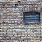 Old brick wall with a small, arched, cobweb-covered window.