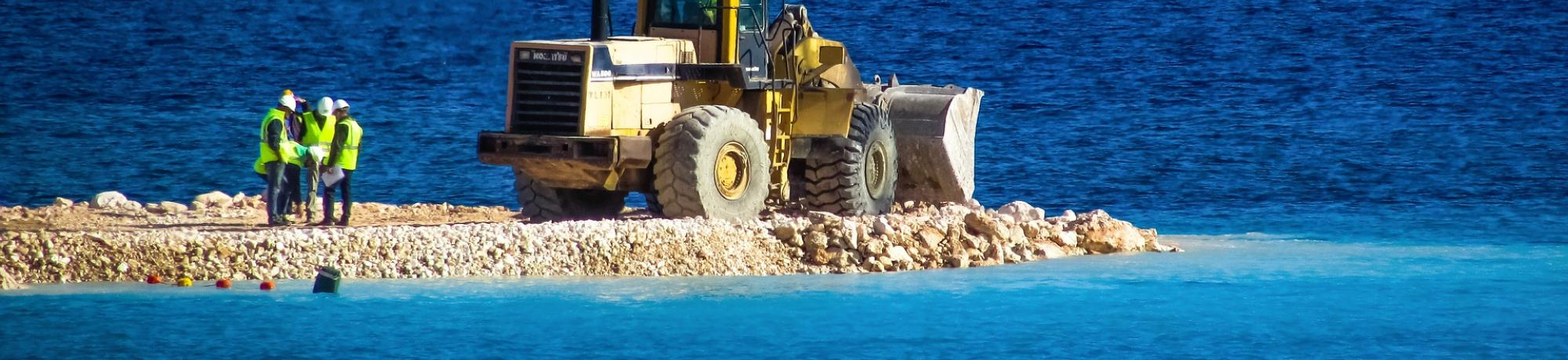 Three construction workers conferring next to a bulldozer, all of which stand on a small man-made gravel island, surrounded by the sea.